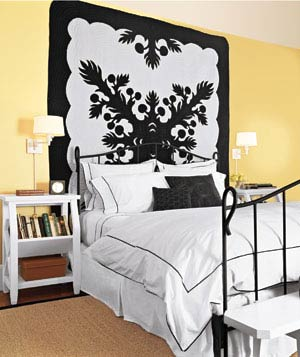 Yellow bedroom with bold black and white graphic hanging quilt
