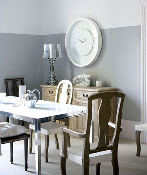 Dining room with gray walls, gray flooring, chrome table and large white clock