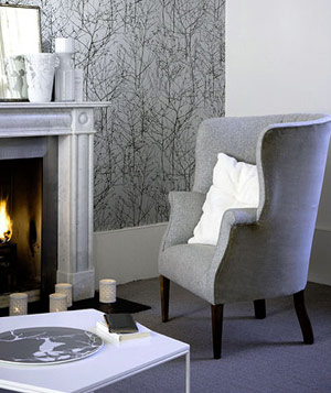 Living room with gray patterned walls, gray carpet, chair and accents and fireplace