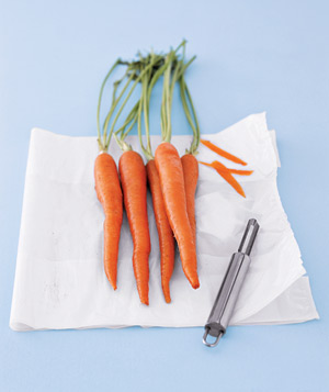 Carrots and peeler on a plastic bag
