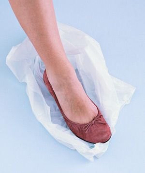 Woman wearing shoe stepping into bag
