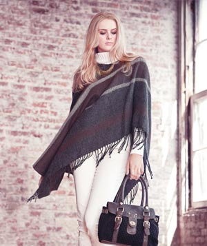 Model wearing white slacks and turtleneck sweater, striped poncho and holding knit and faux-leather handbag