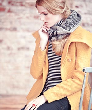 Model wearing yellow jacket, thick grey scarf, striped shirt and dark jeans