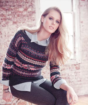 Model wearing patterned sweater over striped blouse with grey leggings