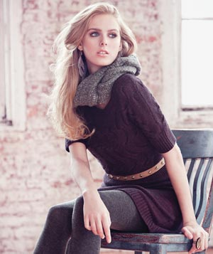 Model wearing purple knit tunic with skinny beige belt and grey tights