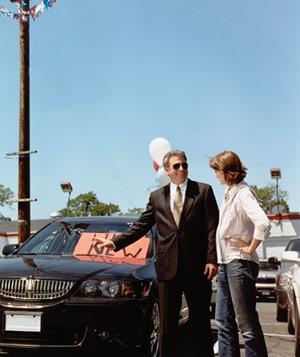 Used car salesman talking to a woman at an automobile lot