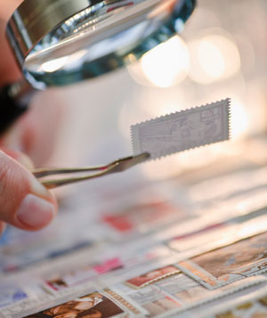 Examining stamp under magnifying glass