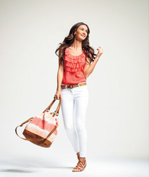 Model wearing white jeans ruffle shirt canvas bag accessories