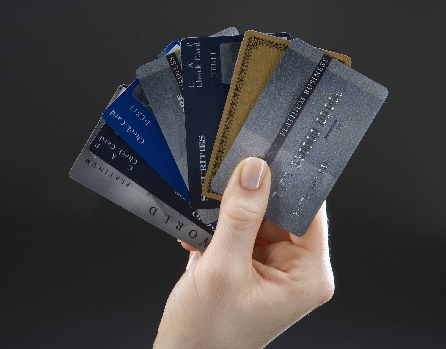 Woman holding set of fanned-out credit cards, close-up of hand