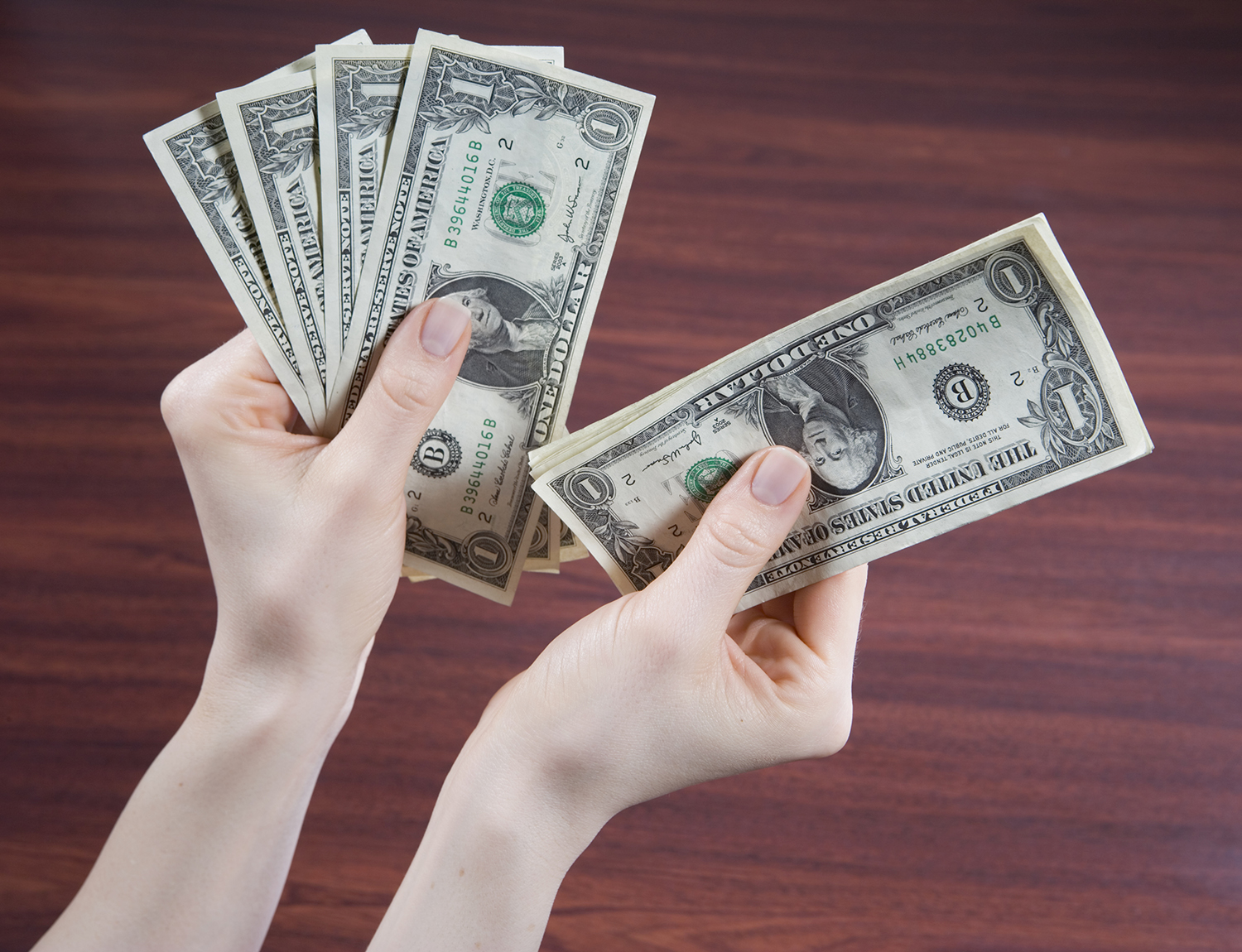 Woman counting US banknotes, close-up of hands