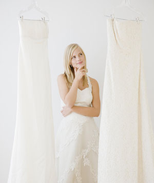 Young woman deciding between wedding dresses