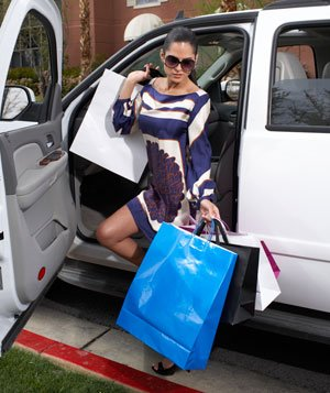 Woman with shopping bags getting out of SUV