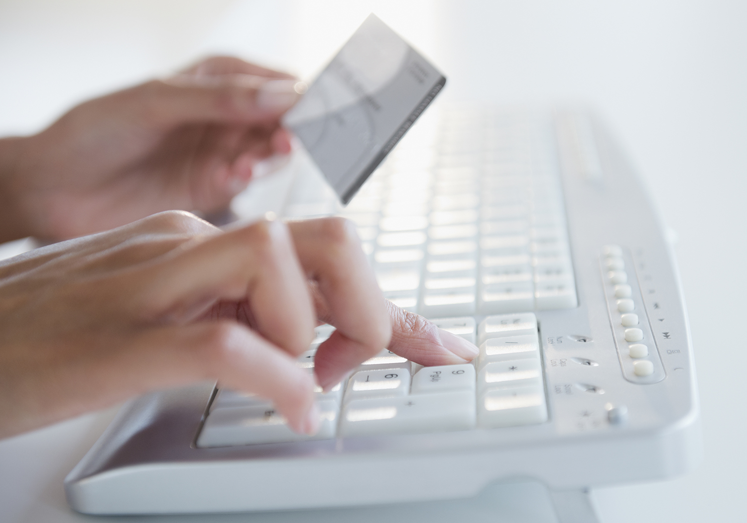 Hands holding credit card while typing on computer keyboard