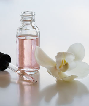 Fragrance in glass bottle with eyedropper and flower
