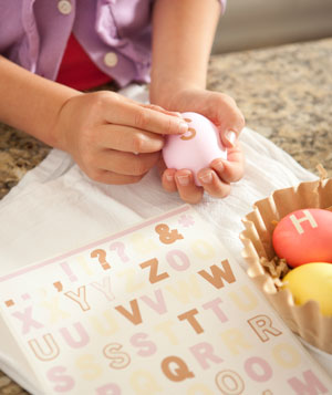 Hands applying letter stickers to Easter eggs