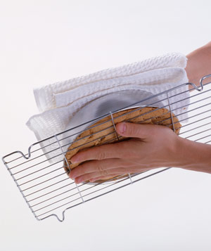 Hands holding wire rack against baked cake in cake tin, upside down