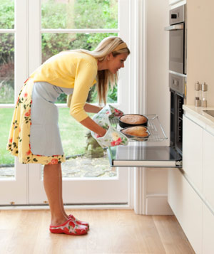 Woman takes cakes out of oven