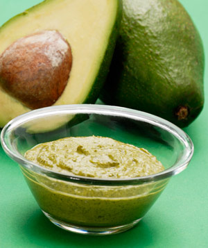 Guacamole with avocados on green background