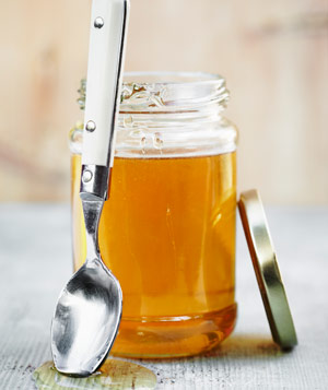 A jar of honey with spoon