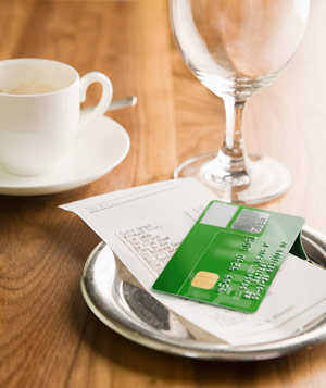 Restaraunt bill and credit card on table with empty glasses
