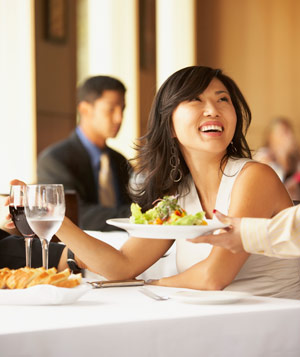 Woman smiling and receiving food at restaurant
