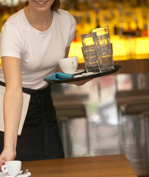 Young waitress holding tray in bar, clearing table, smiling