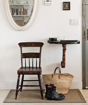Home entrance with wall-mounted table, antique mirror, chair, rug, basket and black boots