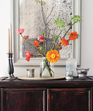 Arangement of poppies, candle holders and candlesticks in front of a mirror