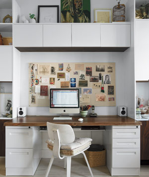 Home office with hardwood desk, collage bulletin board, white custom cabinets