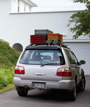 SUV parked outside house with roof rack loaded with luggage