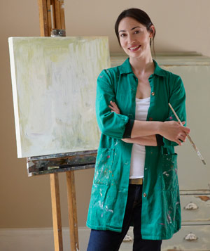 Artist with paintbrush standing in front of her canvas