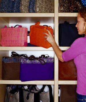 Woman looking at shelf of colorful handbags