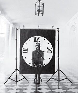 Black and white photograph of a woman with sunglasses sitting behind a giant clock