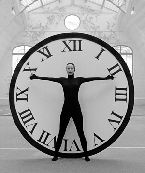 Black and white photograph of woman in black cat suit in front of giant clock facing camera