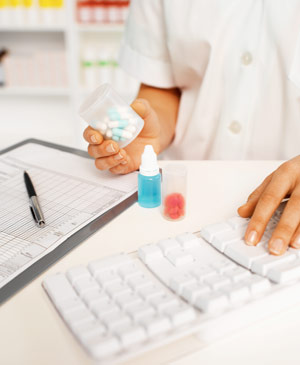Pharmacist with computer keyboard holding container of medicine