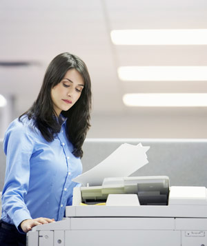 Woman in office using photocopier