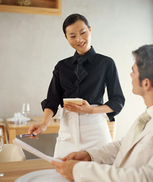 Waitress taking order from man in a restaraunt