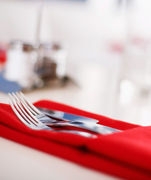 Utensils in a folded red cloth napkin