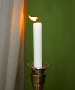 Candle in candlestick with flame blowing out close to a curtain