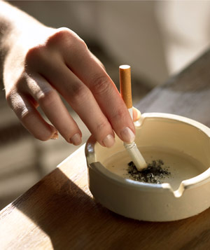 Hand stubbing out a cigarette in an ashtray