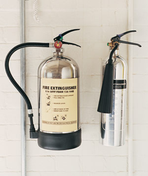 Two fire extinguishers on a painted brick wall