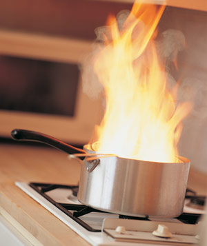 Large fire in metal pot on stovetop