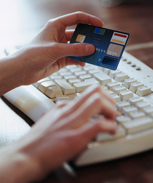 Woman's hands typing on computer keyboard, holding credit card