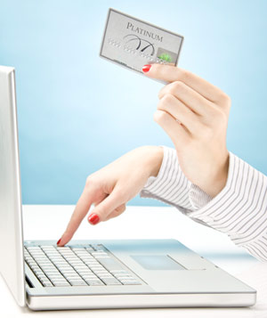 Woman typing on a keyboard and holding a credit card