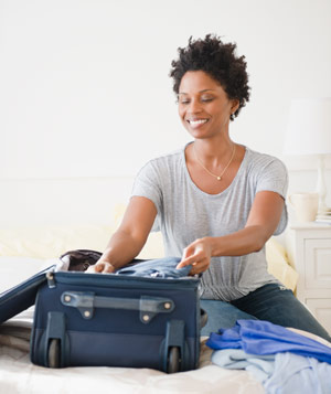 Woman sitting on a bed, packing a suitcase