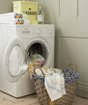 Laundry room with white washing machine, laundry products and wicker laundry basket