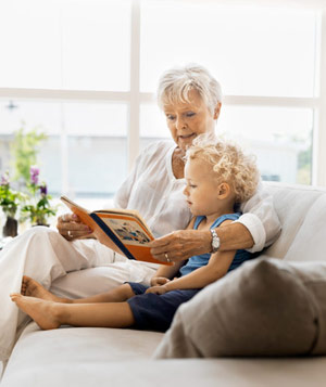 Elderly woman reading to small child