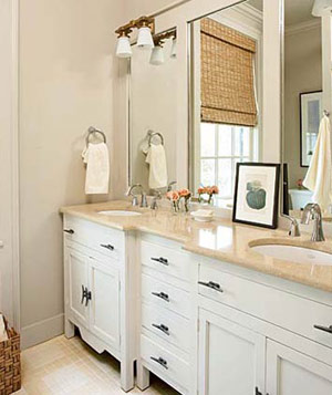 Cream colored bathroom with white cabinetry and light fixtures