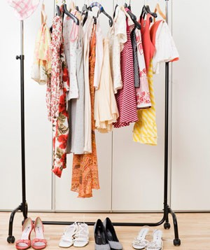 Clothes rack with clothing items hanging and shoes below