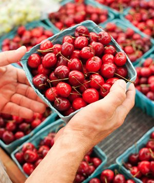 Man holding container of fresh red cherries